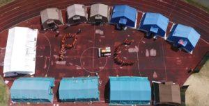 la foto dal drone che immortala il campo base di Mombarone, originale la scritta umana  delle iniziali PC fatta dai ragazzi